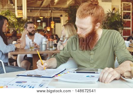 Hipster Freelancer Holding Pencil, Making Notes In Sheets Of Paper With Graphics, Using Digital Tabl