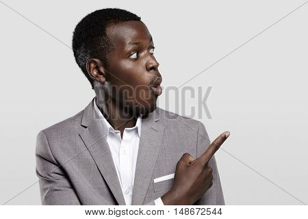 Advertising Concept. Portrait Of Handsome African Entrepreneur Or Office Worker Wearing Suit Pointin