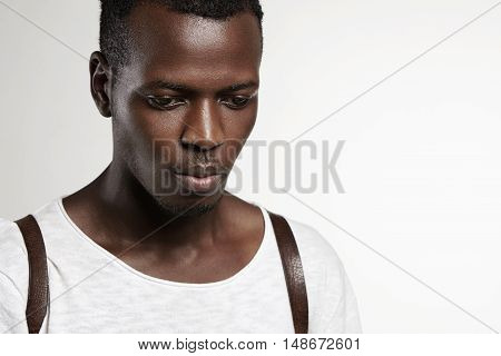 Portrait Of Good-looking Attractive Dark-skinned Male Model Wearing White T-shirt, Looking Down With
