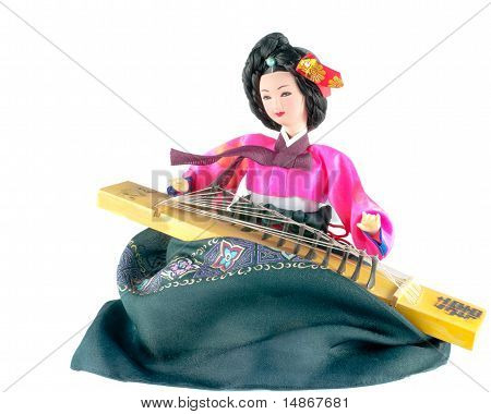 Beautiful Korean doll dressed in traditional costume (hanbok) and playing a traditional Korean string instrument (kayagum).  Isolated on white. poster