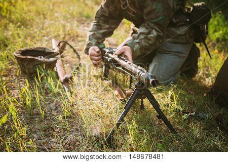 Unidentified Re-enactor Dressed As World War II German Soldier Machine-gunner Reloading A Machine Gun In Summer Forest
