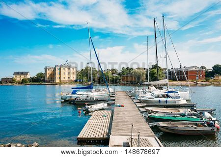 Helsinki, Finland. The Wooden Sea Pier Jetty With Moored Boats And Yachts. The Cityscape Of Harbour And Small Quay In Summer Sunny Day Under Cloudy Sky.