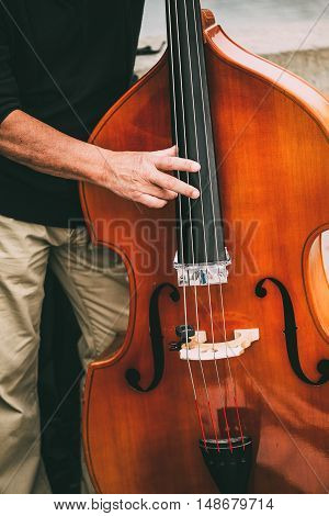 Street Busker Performing Jazz Music Outdoors. Close Up Of Musical Instrument Contrabass.