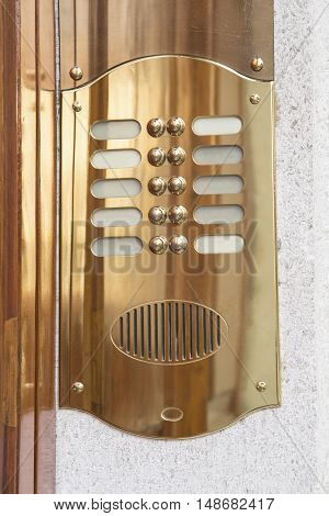 Brass intercom on a marble facade close up
