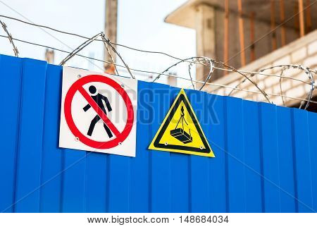 Warning signs and barbed wire on the fence at the construction site. Restricted area