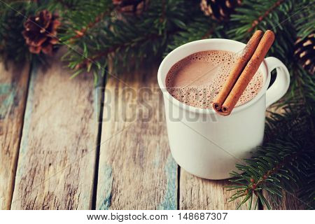 Cup of hot cocoa or hot chocolate on wooden background with fir tree and cinnamon sticks. Traditional beverage for winter time, vintage toning.
