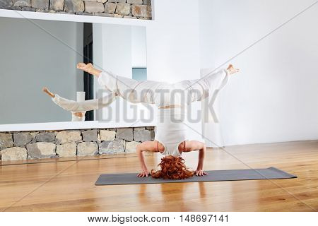 Yoga headstand Sirsasana upside down in wooden floor gym and mirror indoor