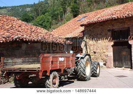 Typical old village of Cantabria Spain. Old tractor on the old street.