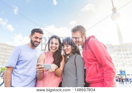 Group Of Friends Looking At Smart Phone In Berlin