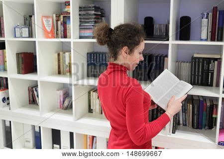 woman standing near shelves with books and CD-ROMs in room, holding book and reading