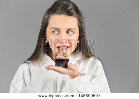 Half-length portrait of woman holding piece of tasty chocolate cake and wants to eat this cake, on gray background