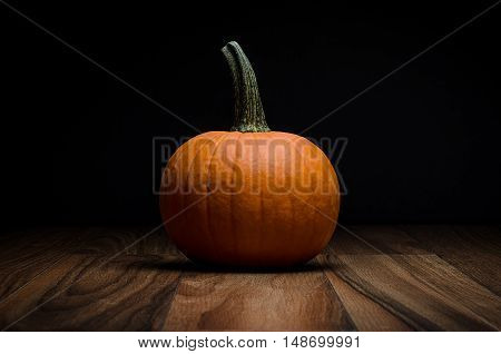 Image of an orange pumpkin on wood surface