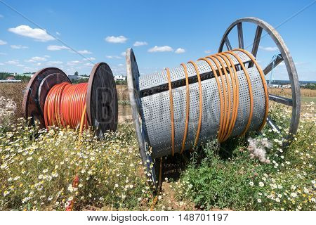 Two cable reels in a building area amidst of wild marguerites