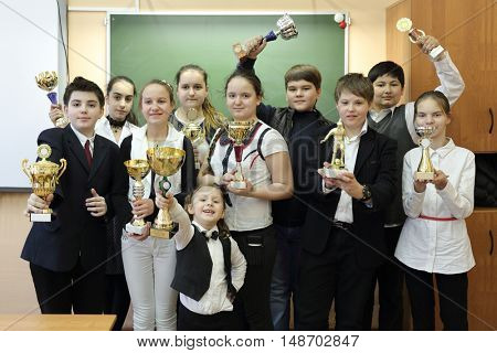 Group portrait of students standing in row in classroom, on background of board, hold sports awards: cups, statuettes