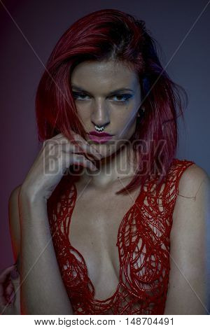 skin and piercing beautiful redhead with pierced nose and red corset lace frills wax