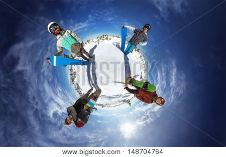 Little planet with bright color snowboarders posing on blue sky backdrop. Sheregesh, Siberia, Russia