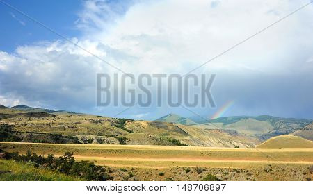 Rainbow appears over distant mountains in Yellowstone National Park.