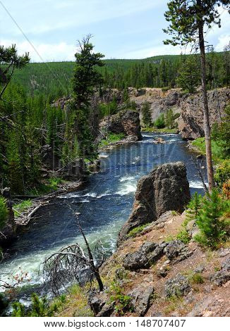 Huge rock clings to shoreline on the Firehole River in Yellowstone National Park. River runs behind rock with rapids and rugged wilderness.