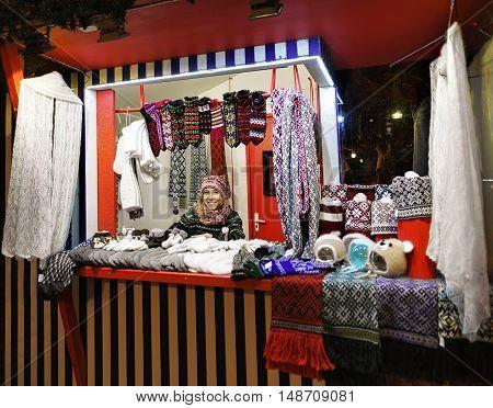 Smiling Woman Sells Warm Clothes At The Riga Christmas Market