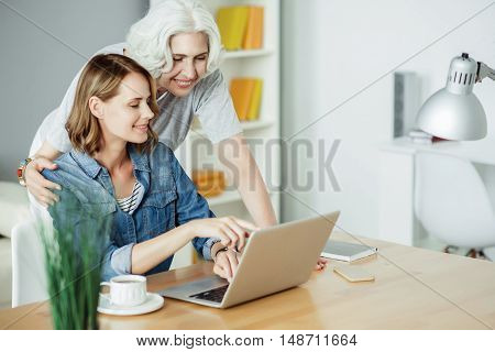 Have a look here. Cheerful beautiful woman sitting at the table and using laptop while pointing the screen to her mother