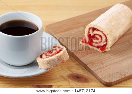 Sweet Roll With Jam On A Cutting Board. Cup Of Tea On A Wooden Table.