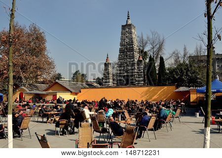 Pengzhou China - November 27 2013: Crowds of Chinese gather to sip tea and relax in the large courtyard in front of the Five Star Pagoda at the Long Xing Temple