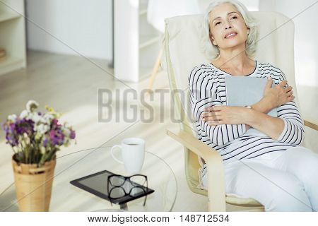 Find peace in mind. Delighted pleasant aged woman crossing her arms and sitting in the arm chair while resting at home
