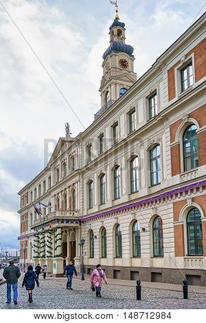 People Walking Near The Building Of Riga City Council
