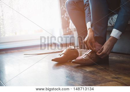 Man dressed in a suit fastens leather shoes. Wedding preparations poster