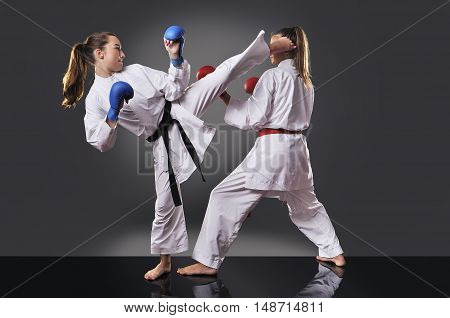 Two Female Young Karate Fighting On The Gray Background