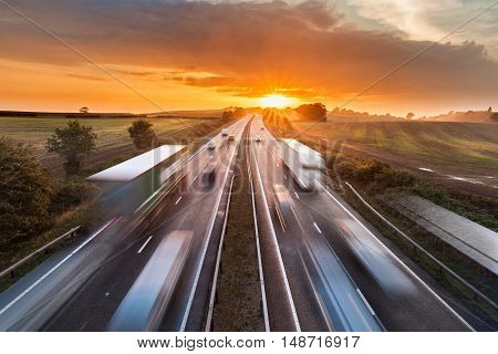 Trucks and Cars in Motion on Busy Motorway at Sunset