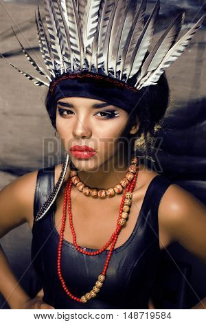 young pretty woman with make up like red indian, feather in hair, fashion hallowen concept creative
