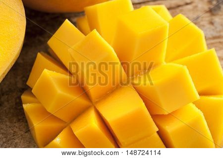 Delicious yellow mango peeled and cut into squares beside other ones on a wooden rustic table