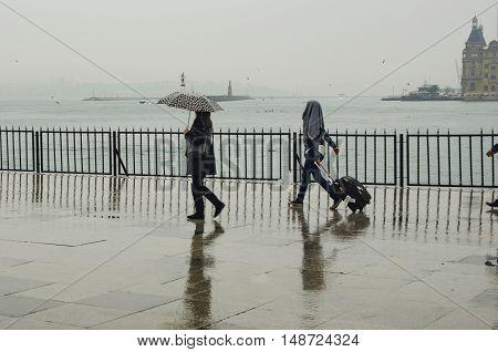 Istanbul Turkey - April 18 2014: Istanbul Kadikoy Steamboat pier. People walking in the rain pier. Strait of Istanbul Kadikoy Pier ferries are the most popular form of public transport in Istanbul for.