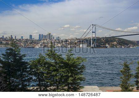 View of the European side of Istanbul from the Bosphorus. The Bosphorus Bridge (Turkish: Bogazici Koprusu) also called the First Bosphorus Bridge is one of two suspension bridges spanning the Bosphorus strait (Turkish: Bogazici) in Istanbul Turkey; thus c