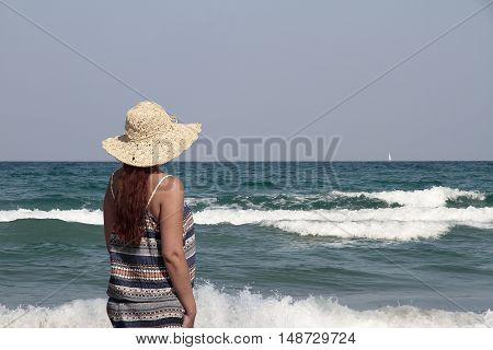 woman back with a pamela looking to the sea with a sailboat in the background on the right