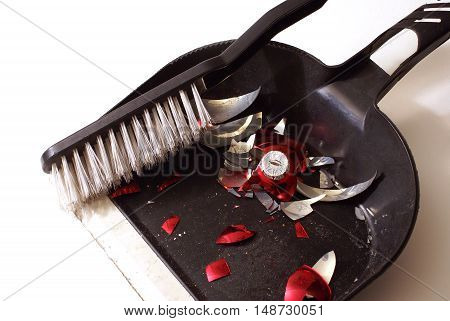 A smashed red holiday bauble has fallen to many pieces so a broom and dustpan come to clean up the mess.
