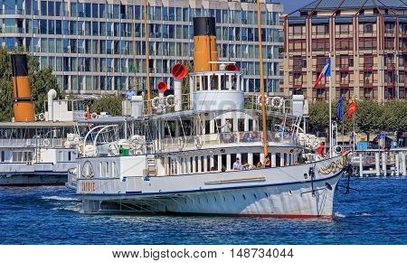 Geneva, Switzerland - 24 September, 2016: MS Savoie on Lake Geneva buildings on Quai du Mont-Blanc quay in the background. Lake Geneva is a lake on the north side of the Alps, shared between Switzerland and France.