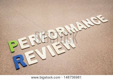Performance review text on brown background - concept of quality measurement