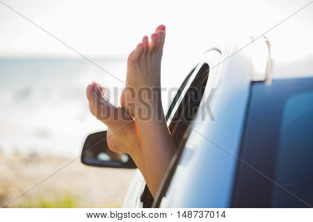 summer vacation, holidays, travel, road trip and people concept - close up of young woman feet showing from car window