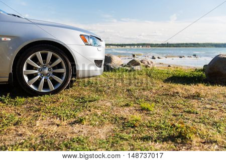 summer vacation, holidays, travel, road trip and transport concept - close up of car parked on sea shore or beach