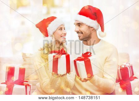 christmas, holidays and people concept - happy couple in santa hats exchanging gifts at home over lights