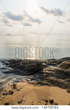 Rock on the beach with calm sea during sunrise in dawn at Ao Lung Dam beach in Samet island Thailand.