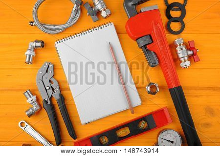 Notebook and plumber tools on yellow wooden background