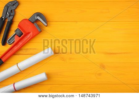 Plumber tools and blueprints on yellow wooden background
