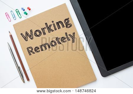 Text Working remotely on brown paper book on table / business concept