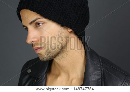Handsome male wearing a bonnet over a gray background