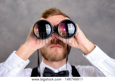 Young Bearded Man Looking Through A Binoculars