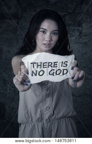 Picture of atheist teenage girl holding a paper with text THERE IS NO GOD