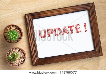 Update, text message on wood frame board on wood table / business concept / Top view